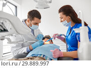 Купить «dentist treating kid teeth at dental clinic», фото № 29889997, снято 22 апреля 2018 г. (c) Syda Productions / Фотобанк Лори