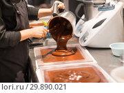 Купить «confectioner makes chocolate dessert at sweet-shop», фото № 29890021, снято 4 декабря 2018 г. (c) Syda Productions / Фотобанк Лори