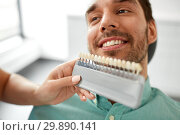 Купить «dentist choosing tooth color for patient at clinic», фото № 29890141, снято 22 апреля 2018 г. (c) Syda Productions / Фотобанк Лори