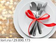 Купить «cutlery tied with red ribbon on set of plates», фото № 29890173, снято 9 февраля 2018 г. (c) Syda Productions / Фотобанк Лори