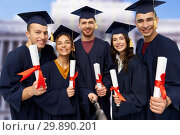 Купить «happy graduates with diplomas taking selfie», фото № 29890201, снято 10 ноября 2018 г. (c) Syda Productions / Фотобанк Лори