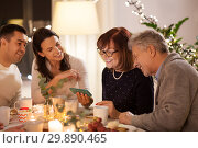 Купить «happy family with smartphone at tea party at home», фото № 29890465, снято 15 декабря 2018 г. (c) Syda Productions / Фотобанк Лори