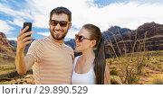 Купить «couple taking selfie by smartphone on grand canyon», фото № 29890529, снято 15 июля 2018 г. (c) Syda Productions / Фотобанк Лори