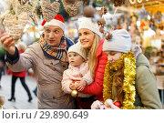 Купить «Family buying Christmas decorations», фото № 29890649, снято 18 декабря 2018 г. (c) Яков Филимонов / Фотобанк Лори