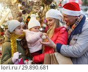 Купить «Parents with daughters choosing Christmas toys», фото № 29890681, снято 18 декабря 2018 г. (c) Яков Филимонов / Фотобанк Лори