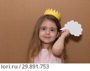 Close up portrait little girl with a crown standing isolated over cardboard background holding speech bubble. Handmade. space for text. Стоковое фото, фотограф Константин Сиятский / Фотобанк Лори