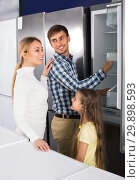 Купить «Happy couple with girl choosing refrigerator», фото № 29898593, снято 20 июля 2019 г. (c) Яков Филимонов / Фотобанк Лори
