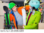 Купить «Buyers in equipment are choosing ski in store.», фото № 29898689, снято 31 июля 2017 г. (c) Яков Филимонов / Фотобанк Лори