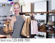 Купить «Female customer holding shopping bags and pair of shoes», фото № 29898789, снято 20 апреля 2019 г. (c) Яков Филимонов / Фотобанк Лори