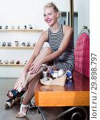 Купить «Female choosing on pair of variety sandals in boutique», фото № 29898797, снято 21 марта 2019 г. (c) Яков Филимонов / Фотобанк Лори