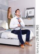 Купить «Man sitting on bed and dressing», фото № 29898965, снято 24 сентября 2018 г. (c) Яков Филимонов / Фотобанк Лори