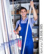 Smiling sellerman is choosing ceiling for client. Стоковое фото, фотограф Яков Филимонов / Фотобанк Лори
