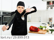 Young woman chef in black uniform posing with big knife. Стоковое фото, фотограф Яков Филимонов / Фотобанк Лори