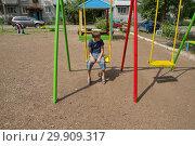 Задумчивый мальчик сидит на качели, на детской площадке во дворе жилого дома. Стоковое фото, фотограф Светлана Попова / Фотобанк Лори