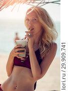 Young slim beautiful girl on sandy beach under Beach umbrella in swimsuit. Стоковое фото, фотограф katalinks / Фотобанк Лори