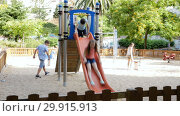 Купить «Cheerful boy and girl play games and running around sliding toy in park», видеоролик № 29915913, снято 23 июля 2018 г. (c) Яков Филимонов / Фотобанк Лори