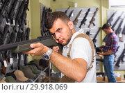 Купить «Portrait of young man which is choosing air-powered gun», фото № 29918069, снято 4 июля 2017 г. (c) Яков Филимонов / Фотобанк Лори