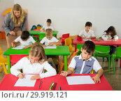 Купить «Female teacher and pupils working in classroom», фото № 29919121, снято 15 ноября 2018 г. (c) Яков Филимонов / Фотобанк Лори
