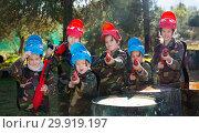 Купить «Friendly group of children paintball players in camouflage posing with guns on paintball playing field outdoors», фото № 29919197, снято 24 ноября 2018 г. (c) Яков Филимонов / Фотобанк Лори