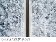 Snow covered forest in winter with road cutting through. White winter wonderland. Стоковое фото, фотограф Mikhail Starodubov / Фотобанк Лори
