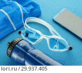 Купить «Flat lay composition with Goggles, swimming cap, smartphone, earphones, fitness tracker and bottle of water equipment for swimming pool on blue background. top view. Swimming set», фото № 29937405, снято 5 февраля 2019 г. (c) Евгений Бобков / Фотобанк Лори