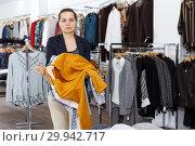 Купить «Woman holding lot of hanger with clothes», фото № 29942717, снято 10 октября 2018 г. (c) Яков Филимонов / Фотобанк Лори