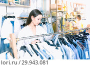 Купить «Woman customer choosing blue blouse in the fashion store», фото № 29943081, снято 15 марта 2018 г. (c) Яков Филимонов / Фотобанк Лори