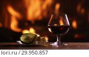 Купить «Still life of a glass of brandy and plate with cheese and lemon on the background of a burning fireplace», видеоролик № 29950857, снято 12 февраля 2019 г. (c) Алексей Кузнецов / Фотобанк Лори