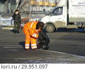 Купить «Работник коммунальной службы собирает мусор в пакет на дороге. Амурская улица. Округ Гольяново. Город Москва», эксклюзивное фото № 29951097, снято 21 января 2015 г. (c) lana1501 / Фотобанк Лори