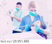 Купить «Female dentist performing treatment for girl with assistant», фото № 29951885, снято 1 марта 2018 г. (c) Яков Филимонов / Фотобанк Лори