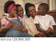 Купить «Happy African American family sitting on the sofa and looking each other», фото № 29960305, снято 7 ноября 2018 г. (c) Wavebreak Media / Фотобанк Лори