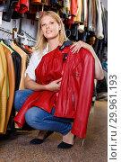 Купить «Positive girl looking for new leather jacket during shopping in retail shop», фото № 29961193, снято 5 сентября 2018 г. (c) Яков Филимонов / Фотобанк Лори