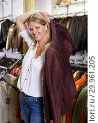 Купить «Woman trying on leather jacket», фото № 29961205, снято 5 сентября 2018 г. (c) Яков Филимонов / Фотобанк Лори