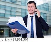 Купить «Man is discussing on the phone a contract», фото № 29961301, снято 3 июня 2017 г. (c) Яков Филимонов / Фотобанк Лори