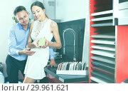 Купить «Positive couple looking at modern kitchen», фото № 29961621, снято 15 июня 2017 г. (c) Яков Филимонов / Фотобанк Лори