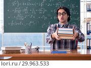 Купить «Young funny math teacher in front of chalkboard», фото № 29963533, снято 20 ноября 2018 г. (c) Elnur / Фотобанк Лори