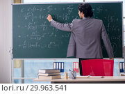 Купить «Young handsome math teacher in classroom», фото № 29963541, снято 20 ноября 2018 г. (c) Elnur / Фотобанк Лори