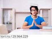 Купить «Young handsome student studying at home», фото № 29964229, снято 31 октября 2018 г. (c) Elnur / Фотобанк Лори