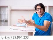 Купить «Young handsome student studying at home», фото № 29964233, снято 31 октября 2018 г. (c) Elnur / Фотобанк Лори