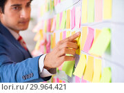 Купить «Young handsome employee with many conflicting priorities», фото № 29964421, снято 16 октября 2018 г. (c) Elnur / Фотобанк Лори