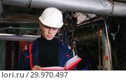 Купить «A man engineer in a helmet and protective glasses making notes in manufacturing plant», видеоролик № 29970497, снято 16 февраля 2019 г. (c) Константин Шишкин / Фотобанк Лори