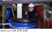 Купить «A man engineer wearing a helmet in manufacturing plant rolls a cart with an empty barrel», видеоролик № 29970545, снято 16 февраля 2019 г. (c) Константин Шишкин / Фотобанк Лори