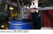 Купить «A man engineer in manufacturing plant rolls a cart with a barrel to a storage», видеоролик № 29970593, снято 16 февраля 2019 г. (c) Константин Шишкин / Фотобанк Лори