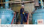 Купить «A man engineer in a helmet walks to a equipment and making notes about manufacturing plant», видеоролик № 29970609, снято 16 февраля 2019 г. (c) Константин Шишкин / Фотобанк Лори