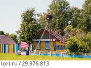 Купить «Storks sit in a nest on a lamppost near a colorful house with a well», фото № 29976813, снято 31 июля 2018 г. (c) Алексей Маринченко / Фотобанк Лори