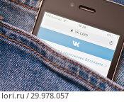 """Купить «Сайт """"Вконтакте"""" на экране телефона. Смартфон лежит в кармане джинсовых штанов», фото № 29978057, снято 17 февраля 2019 г. (c) Екатерина Овсянникова / Фотобанк Лори"""