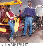 Купить «Dissatisfied African-American man driver of rickshaw talking to young female», фото № 29978297, снято 22 мая 2018 г. (c) Яков Филимонов / Фотобанк Лори