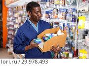 Купить «seller organizing assortment of items on shelves and racks», фото № 29978493, снято 21 января 2019 г. (c) Яков Филимонов / Фотобанк Лори