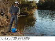 Купить «Man standing with fishing rod», фото № 29978609, снято 27 января 2019 г. (c) Яков Филимонов / Фотобанк Лори