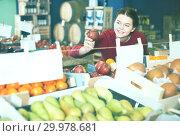 Купить «Portrait of smiling brunette girl buying apple in supermarket», фото № 29978681, снято 1 марта 2017 г. (c) Яков Филимонов / Фотобанк Лори